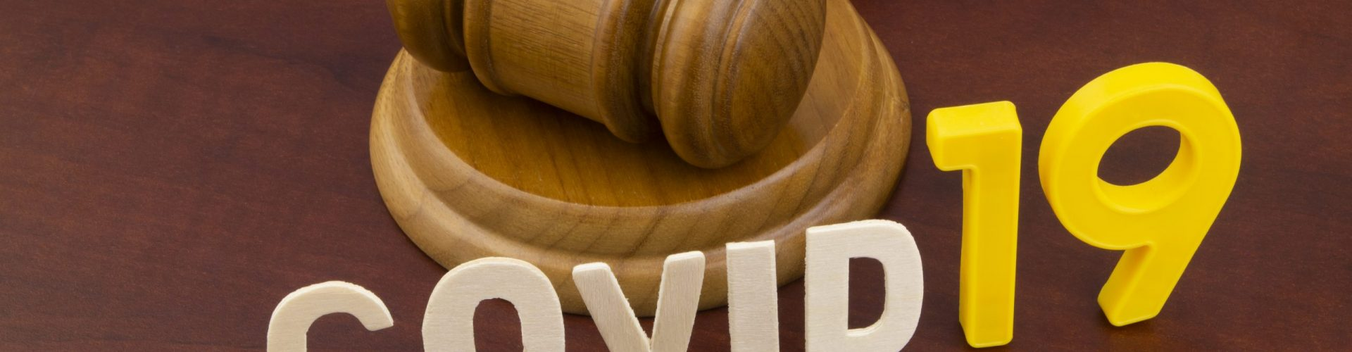 Wooden judge gavel with word covid19. Concept of quarantine and law against covid-19.